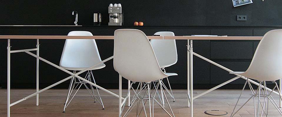 Svart kök med vita stolar och svävande bord.